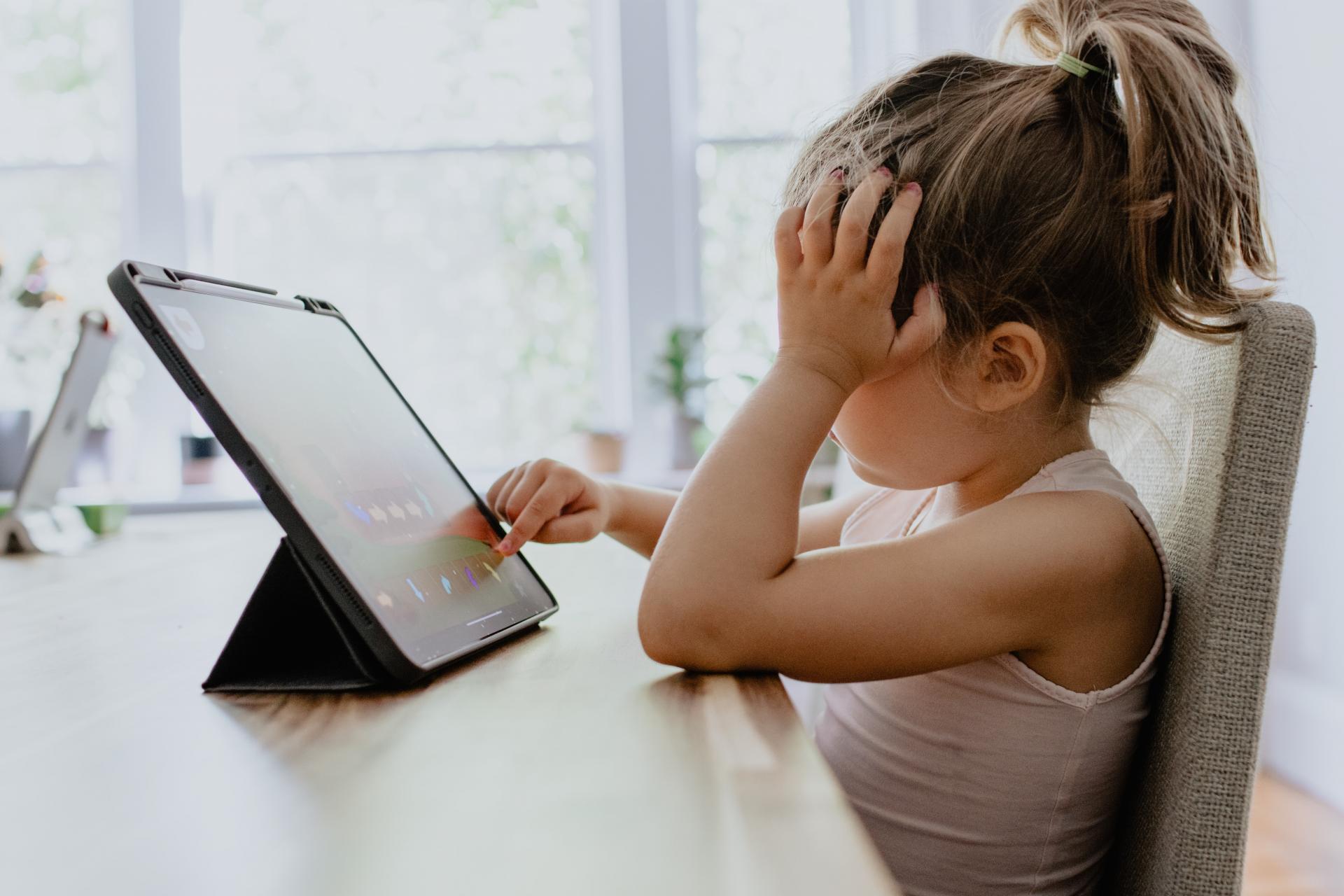 Kind zit spelletje te doen op de ipad